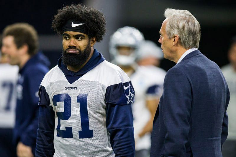 Cowboys running back Ezekiel Elliott (21) talks with Rich Dalrymple, senior vice president of public relations and communications, during OTAs on Wednesday, May 22, 2019, at The Star in Frisco. (Ashley Landis/The Dallas Morning News)