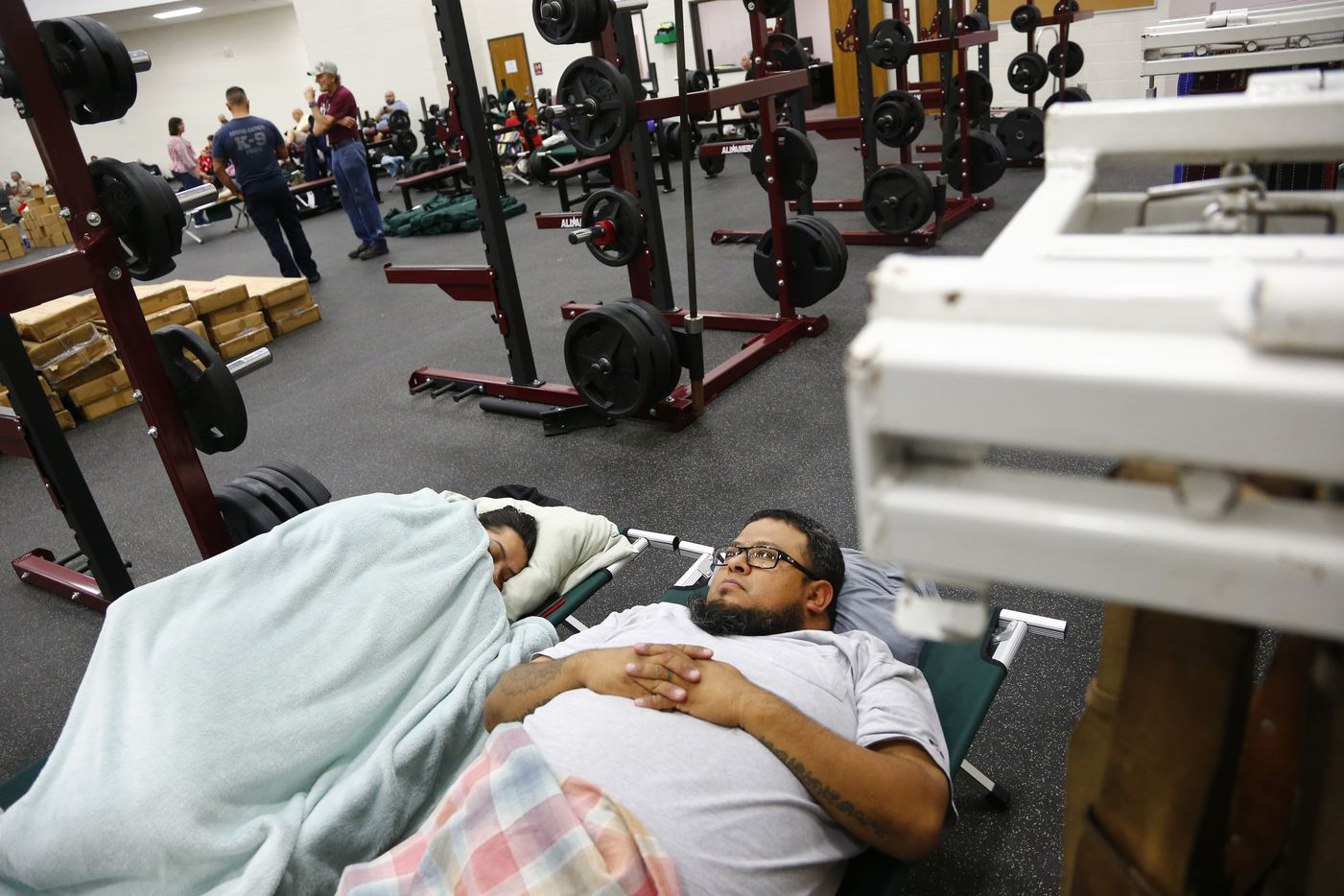 Simon and Stephanie Figueroa sleep in cots in the FEMA dome at Cal Allen High School which was designated for employees of city during Hurricane Harvey in Corpus Christi, Texas on Aug. 25, 2017. The couple were about to leave town and their brother invited them to stay.