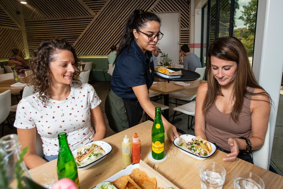 Taco Heads server Guadalupe Barrera, center, serves Allison Ondocsin, left, and Jessica Carney lunch at the new Dallas restaurant.
