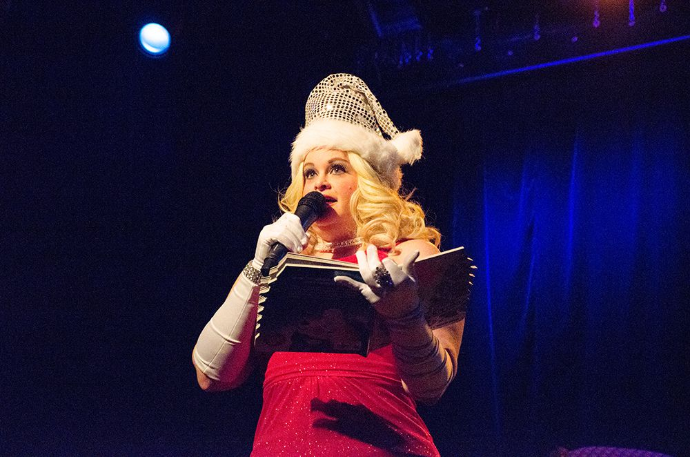 Emcee Violet O'Hara sings naughty Christmas carols with the audience.