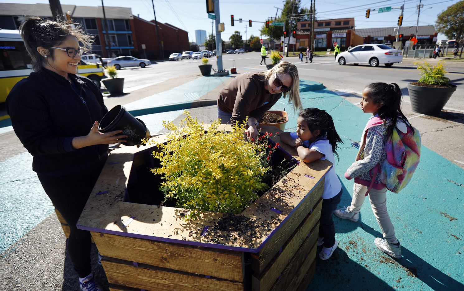 Better Block volunteers Rebecca Castillo (left) and Myria Boehm show children from Jack Lowe Sr. Elementary School the new plants they are filling pots with at the Five Points street intersection in the Vickery Meadow area of Dallas, Friday, November 1, 2019. Improvements include adding a plaza, potted trees a pop-up container store, stage, swings and colorful walkways to beautify the neighborhood. The goal is to reduce crime through improving the environment.
