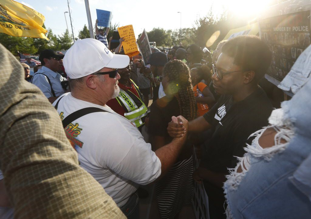 Scott Harmeling (left), who says he supports the McKinney police, finds a point of agreement with an unidentified man who attended the Next Generation Action Network protest in front of the McKinney Police Department in June 2015. (File Photo/Staff)