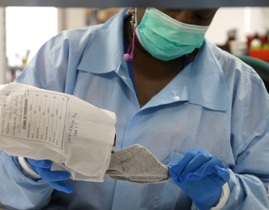 Forensic analyst India Henry removes a pair of underwear from an evidence bag for testing in a sexual assault case in the biology lab at the Houston Forensic Science Center in Houston.