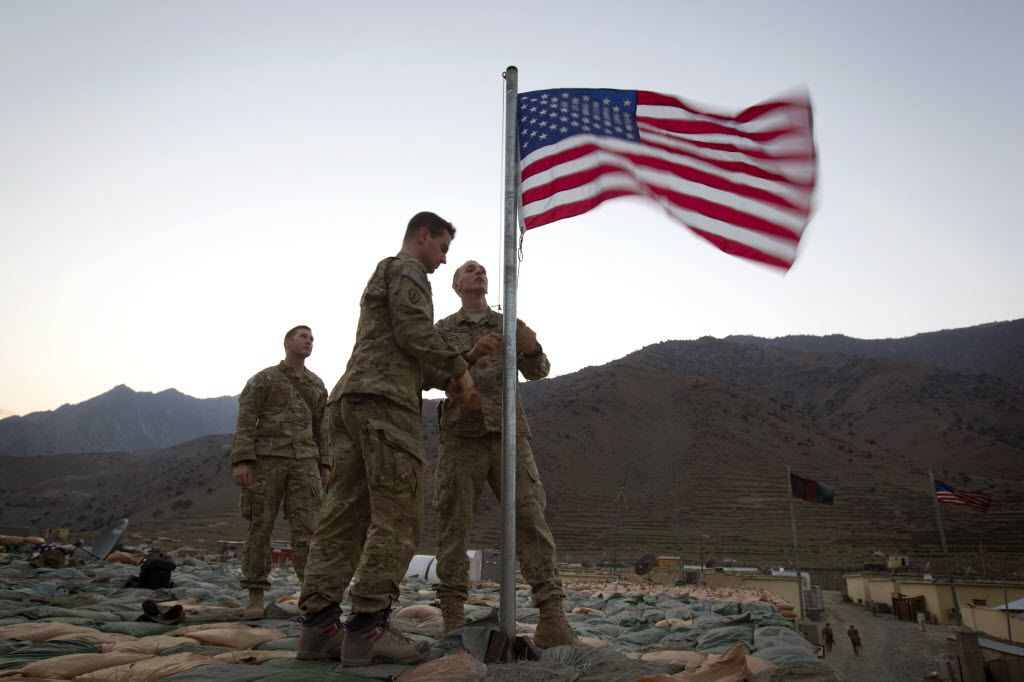 Capt. Erik Schutz, 26, and Capt. Matt Schachman, 28, raise a new American flag to commemorate the 10th anniversary of the 9/11 attacks as Capt. Ron Hopkins, 27, looks on at Forward Operating Base Bostick in Kunar province, Afghanistan.
