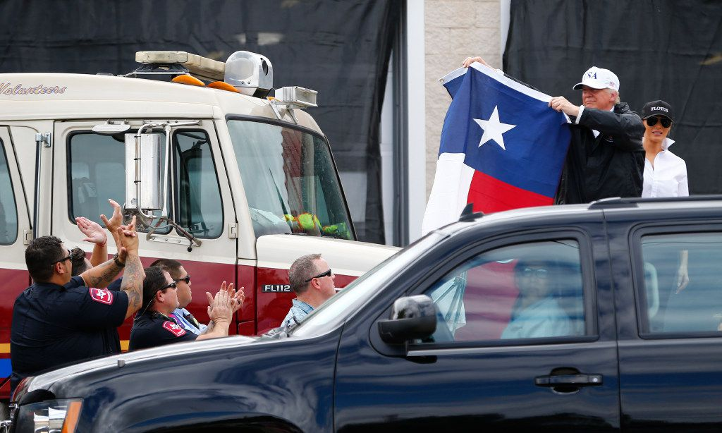 President Donald Trump holds up a Texas flag after attending a briefing from federal, state and local organizations after Hurricane Harvey at Annaville Fire Station 5 in Corpus Christi on Aug. 29, 2017.