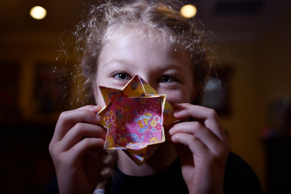 Trinity Adams, 8, with a origami creation she made for her sisters' organization Paper For Water, at the family's home in Dallas, July 24, 2018. Since the organization was launched, the sisters have worked with hundreds of volunteers to raise more than $1.5 million to help fund 160 plus water projects in 17 countries.