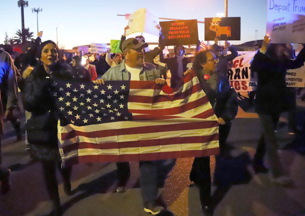 People march on a roadway behind the El Paso County Coliseum where President Donald Trump was scheduled to speak at a rally, Monday, Feb. 11, 2019, in El Paso, Texas. The counter-rally was organized by local activist organizations and former U.S. Rep. Beto O'Rourke spoke to the crowd.