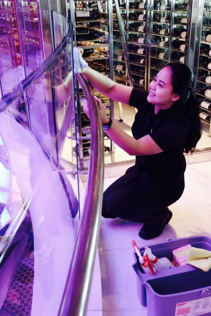 Yulia Asriyani cleans glass in the ship's atrium. She worked in a hotel in her native Indonesia before going through five weeks at the cruise line's academy in Jakarta.
