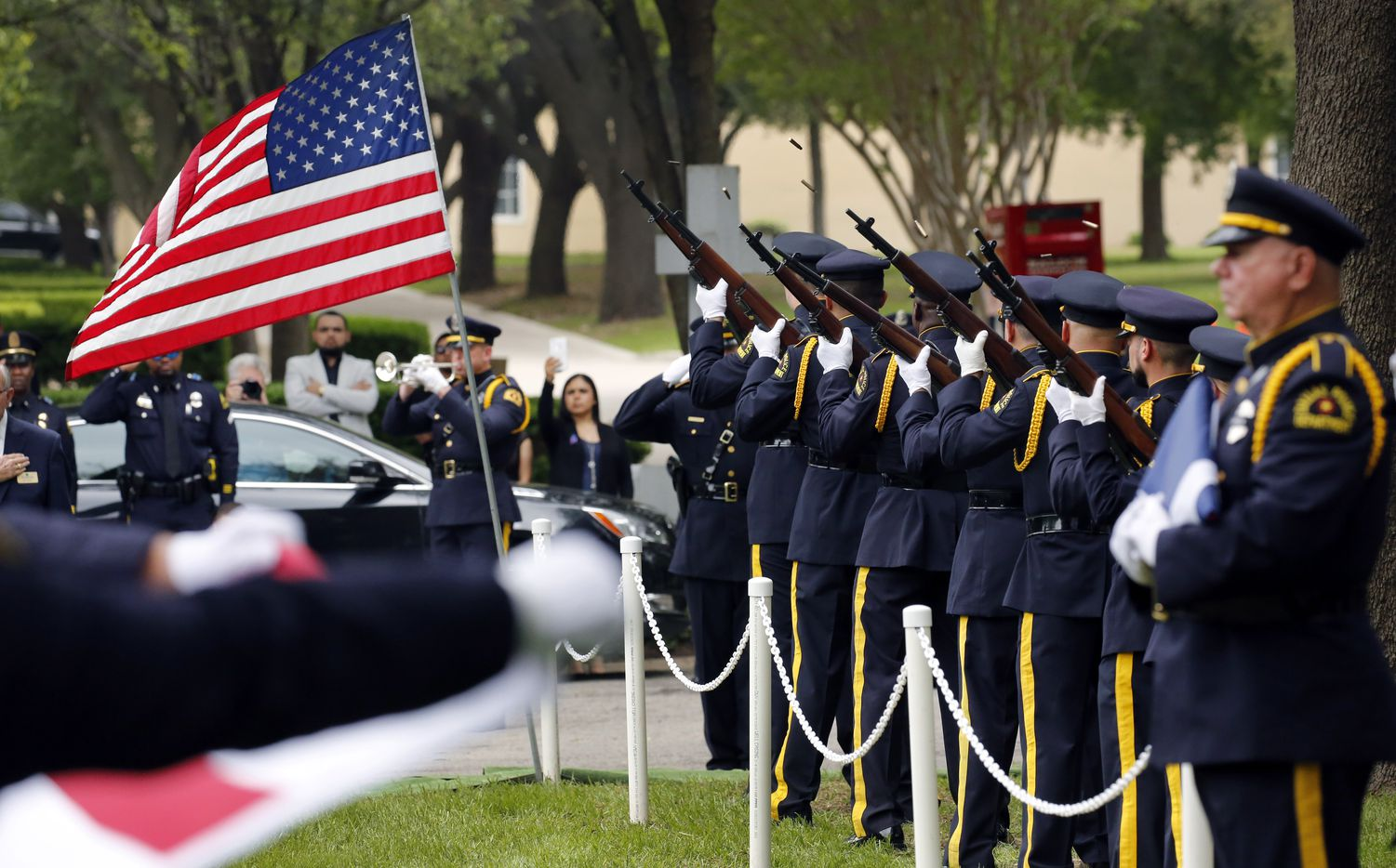 Shell casings fly as a 21-gun salute is performed during the burial of Dallas police Officer Rogelio Santander, Jr., 27, in the Garden of Honor.