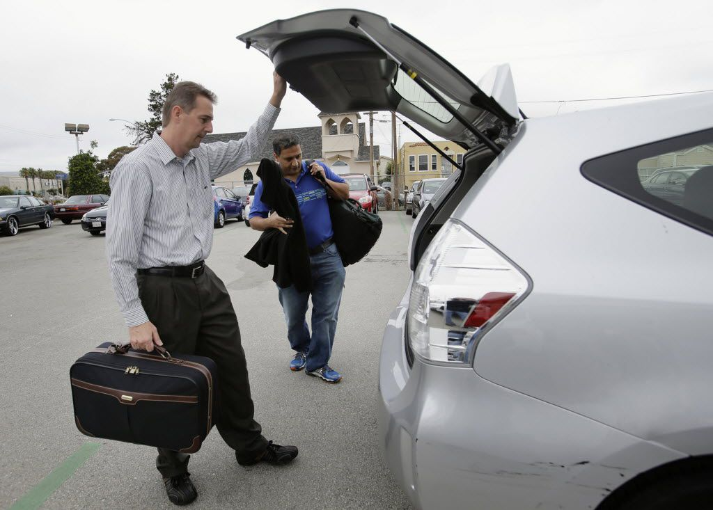John Penny, left, and Marty Puranik load their luggage into a rental Prius in Millbrae, Calif. They just arrived on a business trip from Florida.