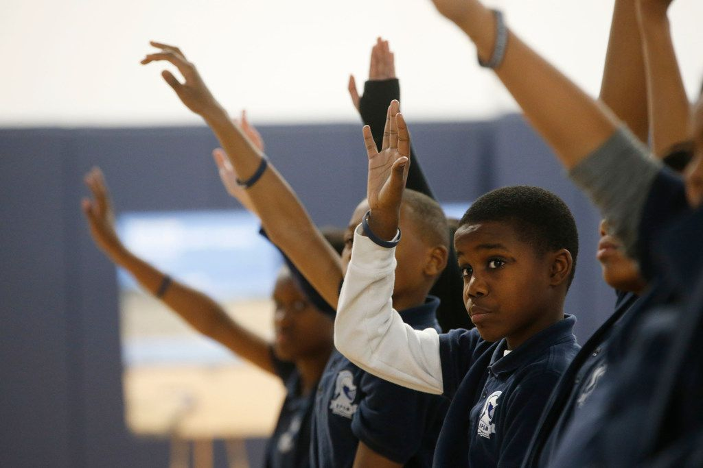 Damarte Richardson, 10, and classmates raise their hands after Andre Agassi asks which students expect to go to college, during a tour of the KIPP Pleasant Grove school in Dallas.