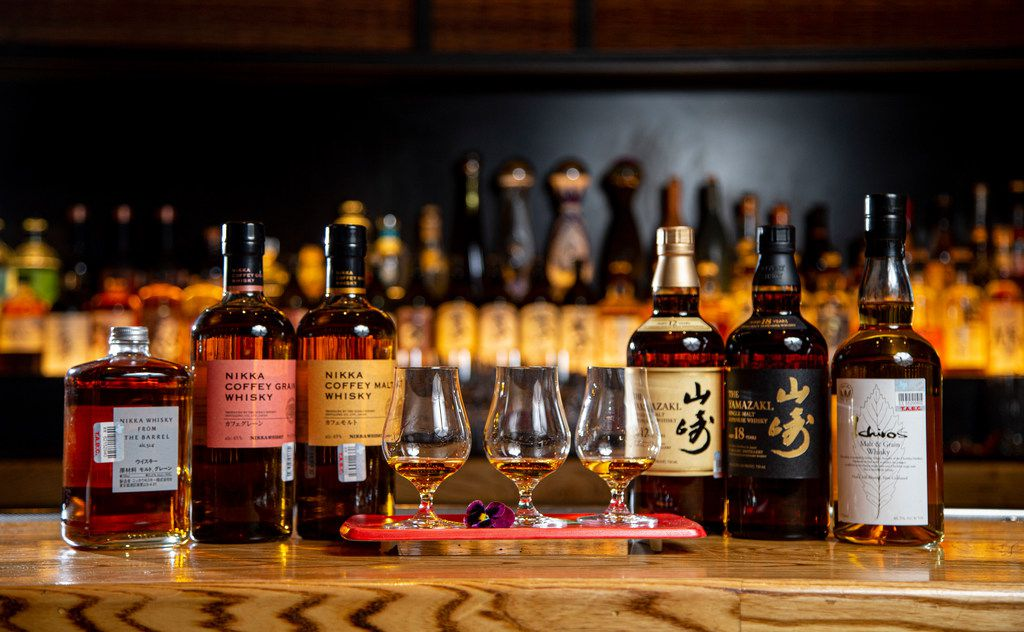 Three flights of Nikka Coffey Grain Whisky flanked by bottles of various Japanese whiskies at Nobu in the Crescent Hotel in Dallas.