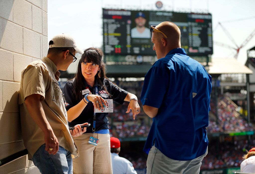 Texas Rangers usher and HKS architectural designer Margarita Aguirre helps fans Leland Tieh (left) of Frisco and Ryan Ballet of Bedford find their section during Opening Day at Globe Life Park in Arlington.