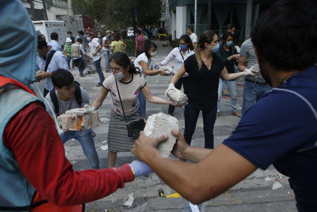 Voluntarios recogen los escombros de un edificio que se derrumbó durante un terremoto en el barrio Condesa de la Ciudad de México, el martes 19 de septiembre de 2017. (AP Foto/Rebecca Blackwell)