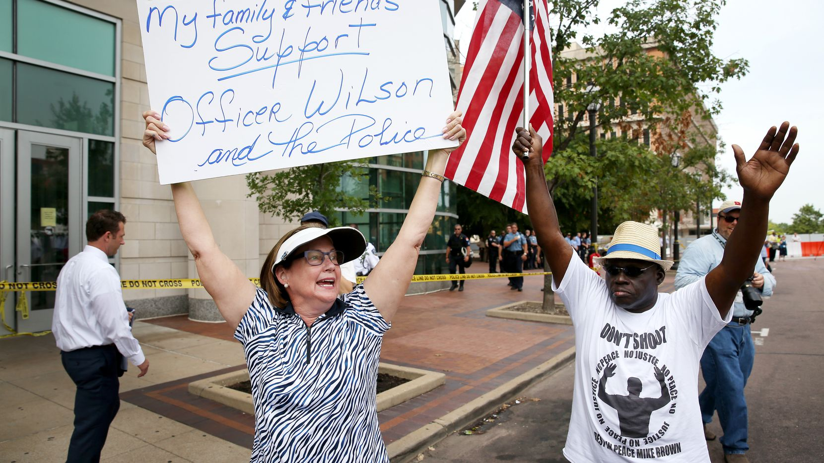"CLAYTON, MO - AUGUST 20:  Patty Canter (L) holds a sign reading, "" My Family & Friends Support Officer Wilson and the Police"", as she walks next to Chris Finch who joined others in front of the Buzz Westfall Justice Center asking for justice for the Michael Brown family including the arrest of Darren Wilson the officer who shot him on August 20, 2014 in Clayton, Missouri. A grand jury will begin looking at the circumstances surrounding the fatal police shooting of an unarmed teenager Michael Brown who was shot and killed by a Ferguson, Missouri police officer on August 9. Despite the Brown family's continued call for peaceful demonstrations, violent protests have erupted nearly every night in Ferguson since his death. (Photo by Joe Raedle/Getty Images)"