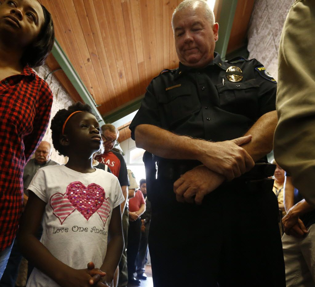 Oluwakemi Ojo, 7, and assistant chief Rodney Thompson attended the prayer service Friday at the Cedar Hill Government Center.