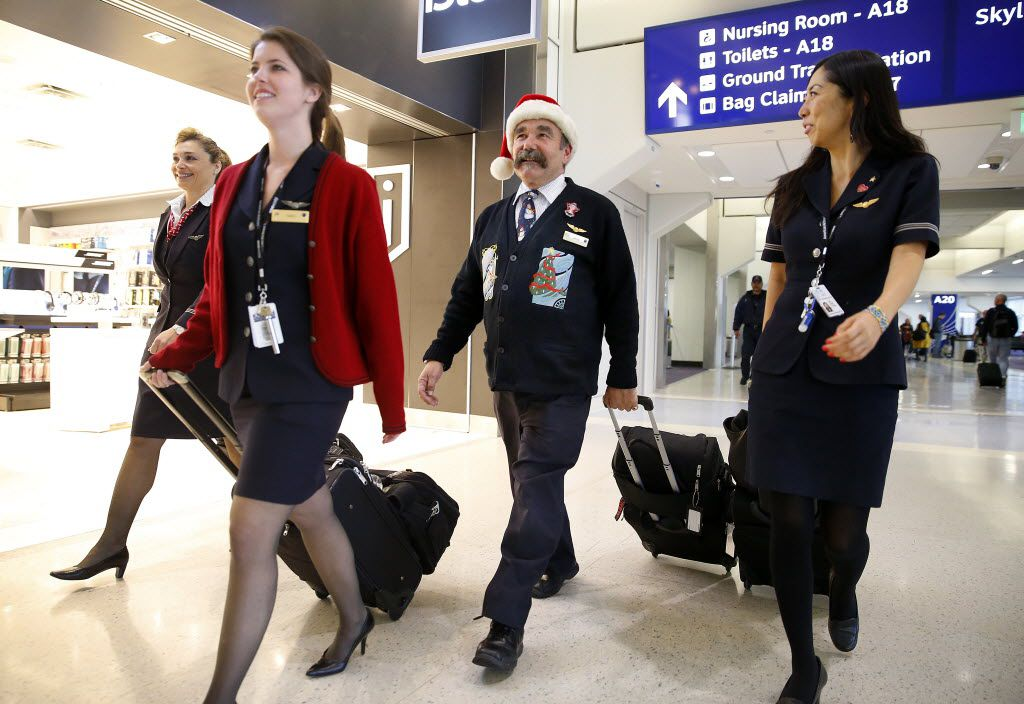 American Airlines Bryan Merton sported a Santa hat as he and fellow flight attendants (from left) Rhonda Ake, Sarah Cowie and Mirei Midorikawa made their way to their Terminal A flight at Dallas Fort Worth International Airport, Thursday, December 18, 2014.
