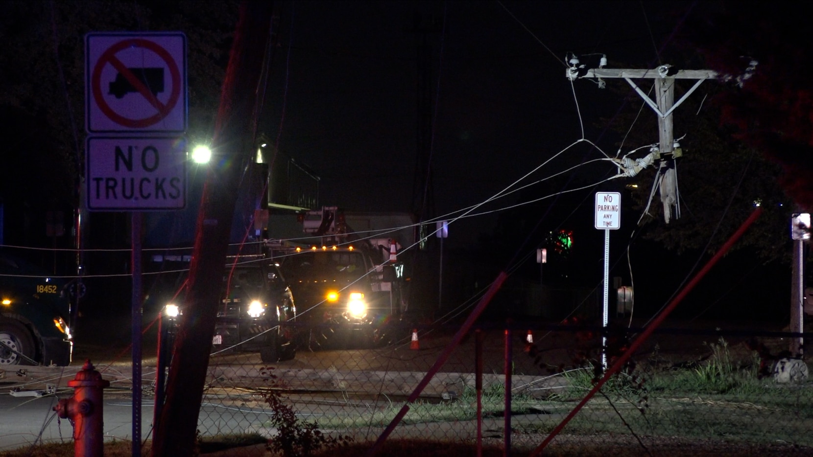 Damaged power lines are visible in Irving after an 18-wheeler knocked down four utility poles in a residential area Monday night.