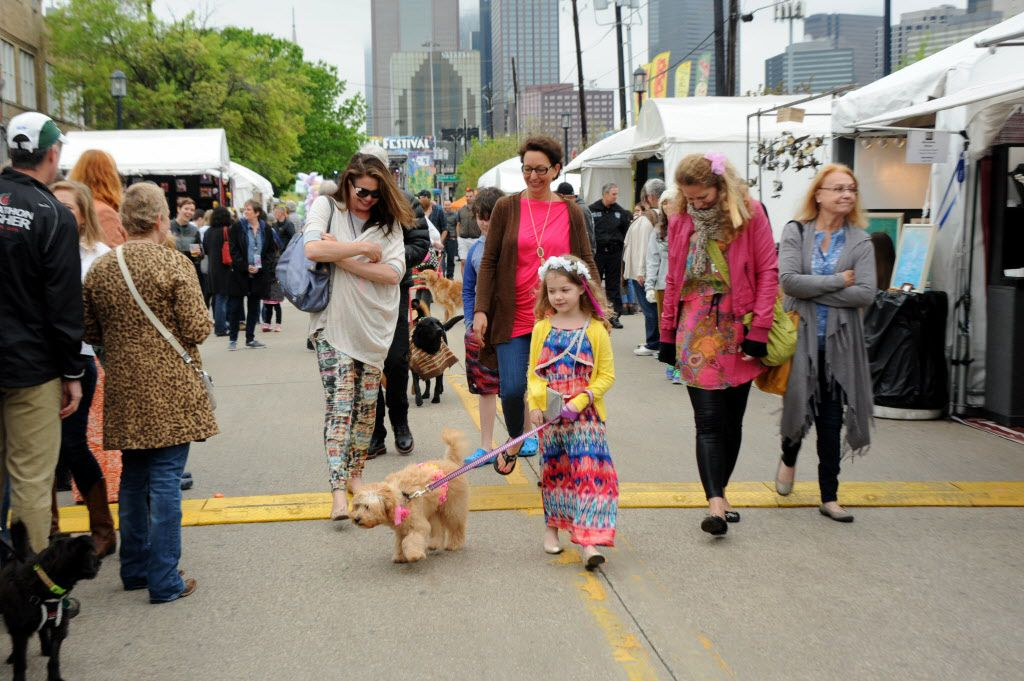 Zettie Niven and her six-month-old goldendoodle Poppy walk in the annual pet parade at the Deep Ellum Arts Festival in Dallas on April 5, 2015.