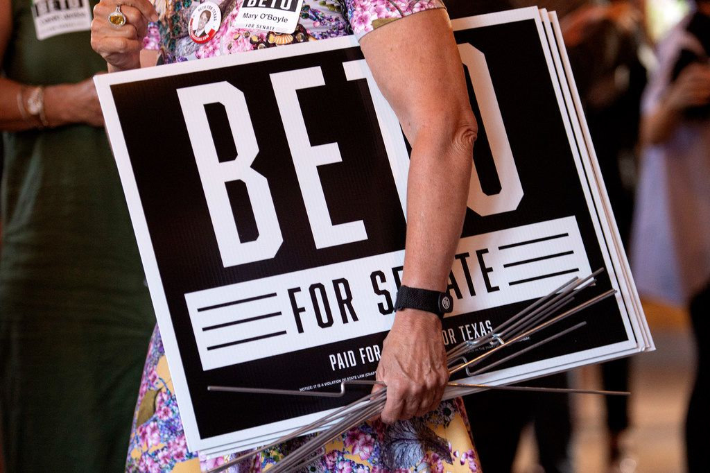 A supporter of Beto O'Rourke, a Democrat looking to unseat incumbent Republican Sen. Ted Cruz, carries campaign signs at a rally, Thursday, May 24, 2018 at Mudhen Meat and Greens in Dallas. (Jeffrey McWhorter/Special Contributor)