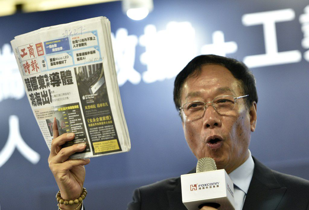 "Terry Gou, Chairman of Taiwan's Foxconn, also known as Hon Hai, displays a Chinese version of the Commercial Times during a press conference in New Taipei City on June 22, 2017. The head of Taiwan's tech giant Foxconn said on June 22 its pursuit of Toshiba ""is not yet over"", a day after the Japanese firm announced it preferred another group of bidders to acquire its prized chip business. / AFP PHOTO / SAM YEHSAM YEH/AFP/Getty Images"