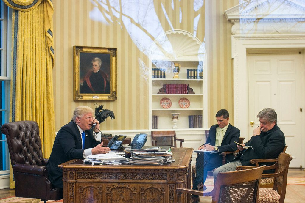 President Trump takes a call Jan. 28, 2017, with National Security Advisor Michael Flynn and Stephen Bannon in the Oval Office. Flynn would soon be fired and on Dec. 1, he pleaded guilty to lying to the FBI.
