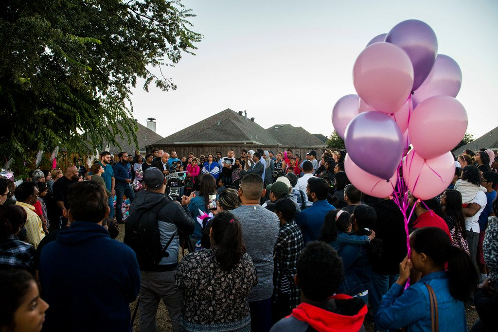 People gather at a memorial for missing 3-year-old Sherin Mathews on Oct. at a tree behind her home in Richardson.