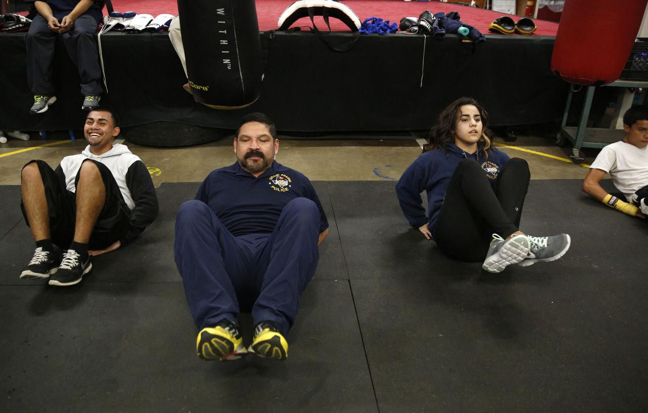Volunteer coach Gerardo Contreras leads Hector Cruz, 20, and Monica Navarro, 17, in a set of crunches at the youth boxing gym in Grand Prairie.