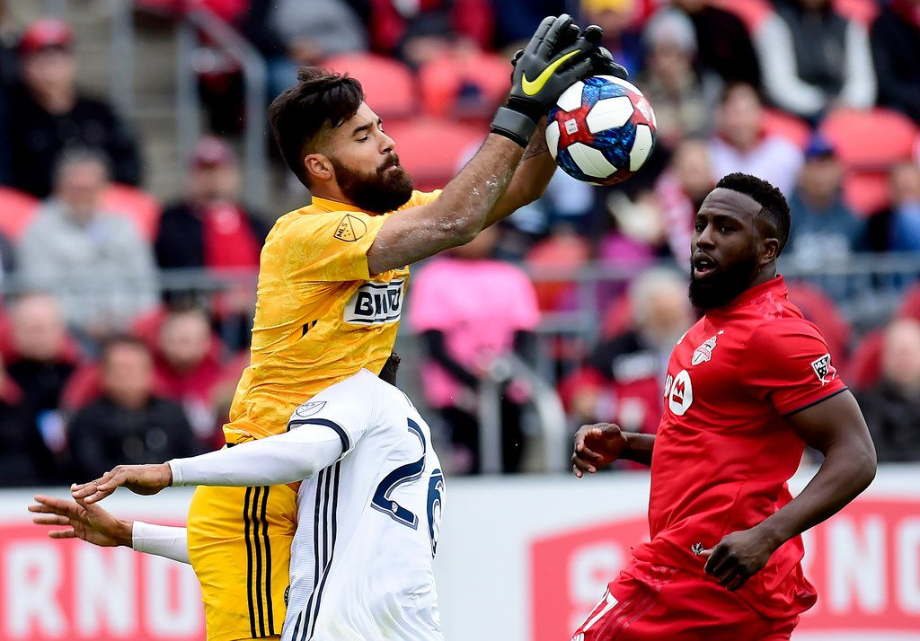 Philadelphia Union goalkeeper Carlos Miguel Coronel (31) makes a save as he collides with teammate Auston Trusty (26) during the second half of an MLS soccer game in Toronto, Saturday, May 11, 2019. T(Frank Gunn/The Canadian Press via AP)