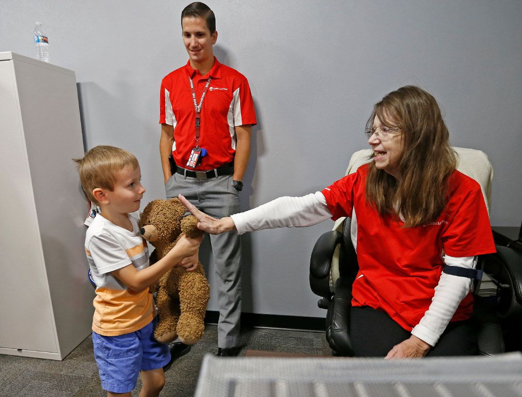 """Luke Swofford (left), 4, holds an arm of his teddy bear named """"Teddy Bear"""" to high five Peggy Geisinger (right), Office Assistant of the Lost and Found, as Airport Security Compliance Officer Ian Fryers, who found Luke's teddy bear, inside the Lost and Found office at Dallas Love Field Airport."""