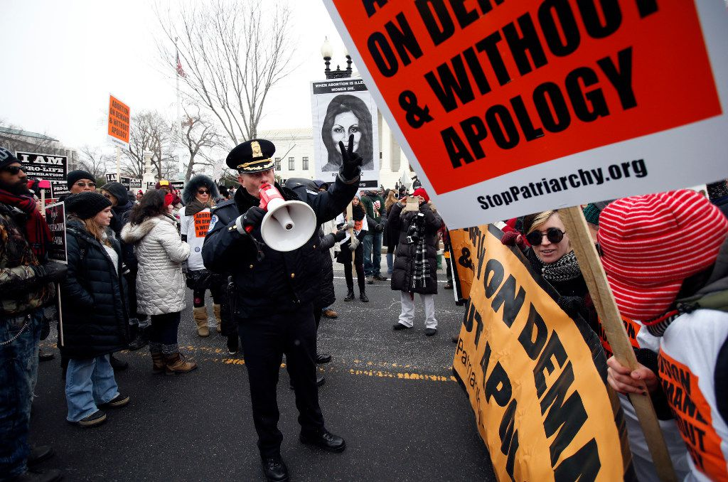 A U.S. Capitol Police officer warned abortion rights demonstrators to move as they attempted to block abortion opponents taking part in the March for Life 2016 outside the U.S. Supreme Court building in Washington in January. (File Photo/The Associated Press)
