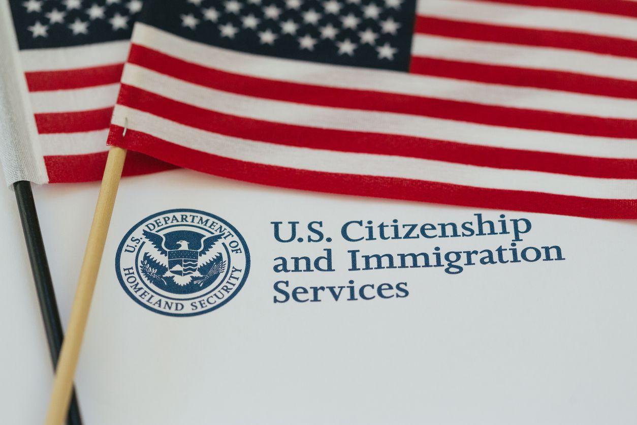 La bandera estadounidense encima de documentos de la agencia de inmigración USCIS. iStock.