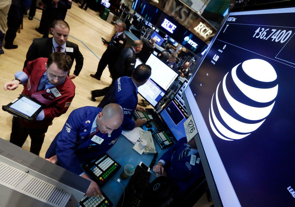 FILE - In this Monday, May 19, 2014, file photo, traders gather at the post that handles AT&T on the floor of the New York Stock Exchange. AT&T is raising prices for its DirecTV Now streaming TV service, while removing some networks from the cable-like television package. (AP Photo/Richard Drew, File)