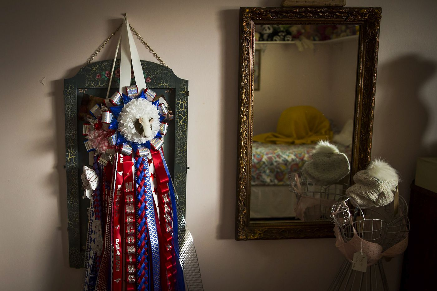 A homecoming mum presented to her by classmates at her school hangs on the wall as Kara Zartler is seen in the mirror, wrapped in her blanket, kneeling on her bed and rocking forward and back, one of her usual calming mechanisms,  on Friday, March 17, 2017, in Richardson.(Smiley N. Pool/The Dallas Morning News)