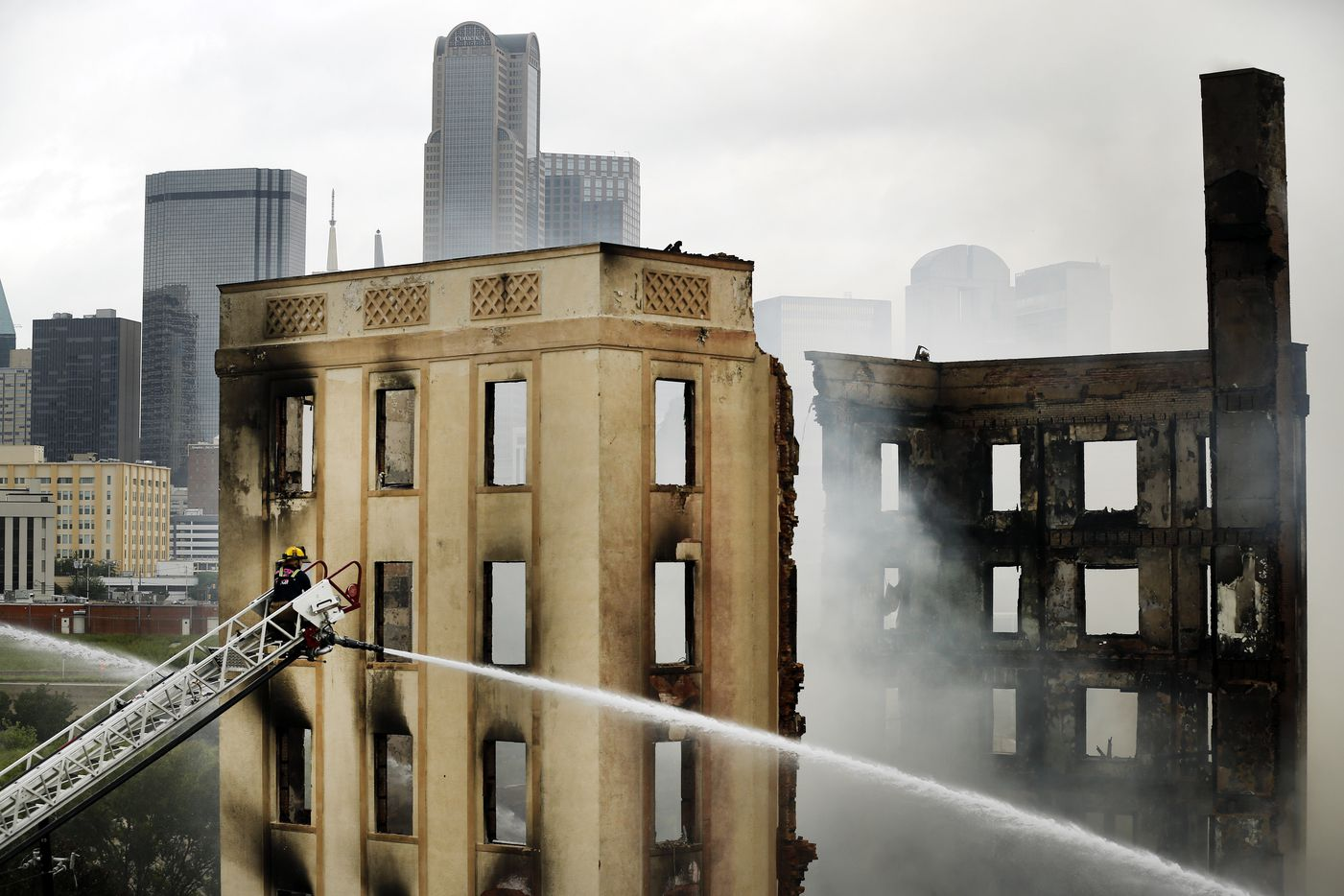 A Dallas firefighter manned an aerial hose pouring water on the destroyed historic Ambassador hotel just south of downtown Dallas on Tuesday morning. Over 100 firefighters responded to the four-alarm fire.