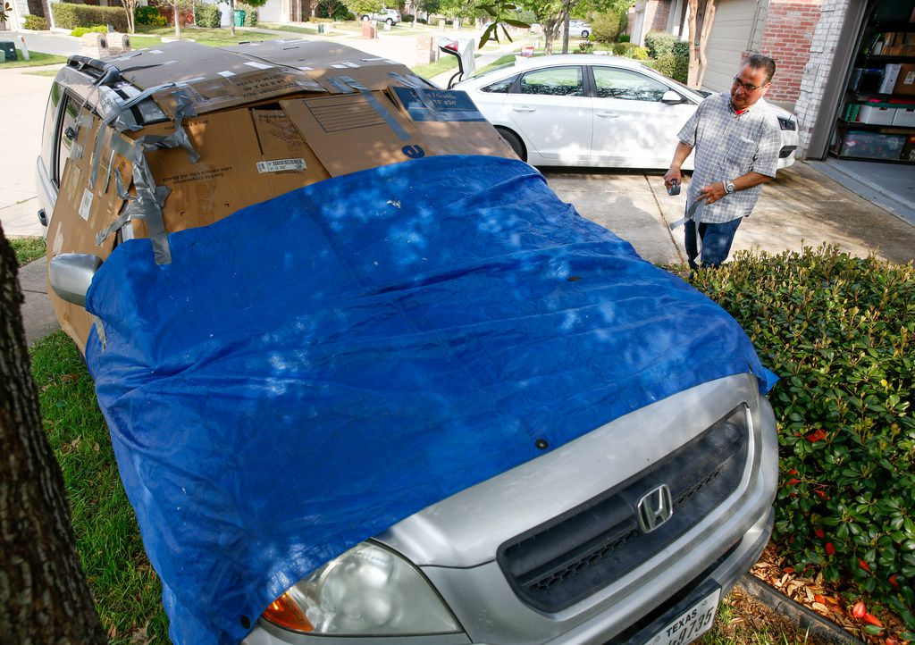 Michael Ruiz of McKinney tapes boxes and a tarp on one of his cars to protect it from hail damage as the threat of storms get closer on April 17, 2019 in McKinney, Texas (Brian Elledge/The Dallas Morning News)