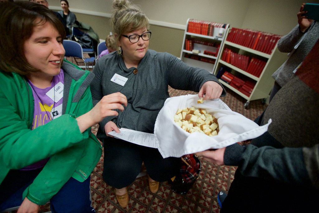 Jacob Smith (right) offers bread to Leah Battalora (left) and Kathryn Williams during communion at The Feast, a service for people with special needs at Highland Park United Methodist Church.