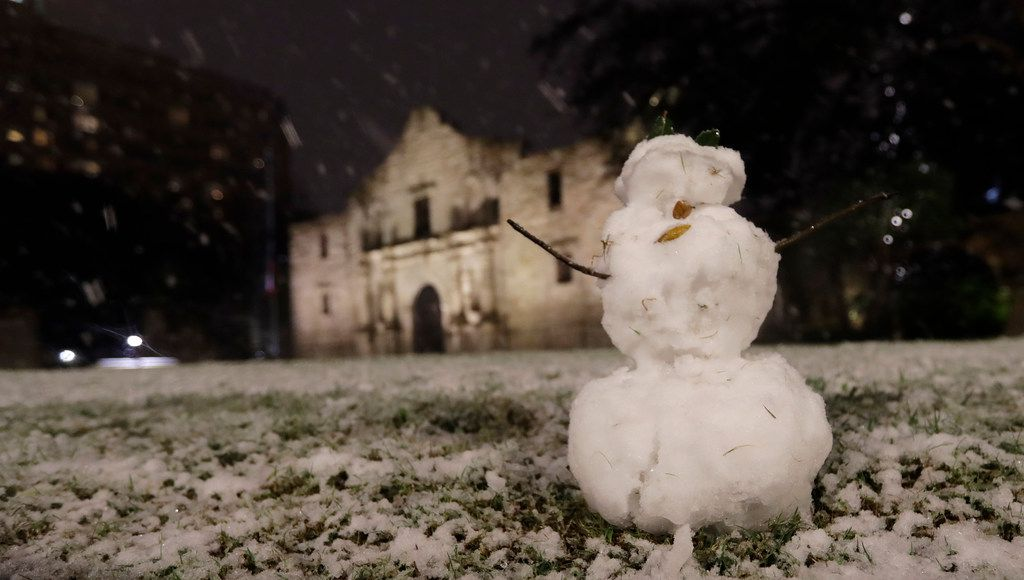 A small snowman stands in front of the Alamo as snow falls in downtown San Antonio, Thursday, Dec. 7, 2017.