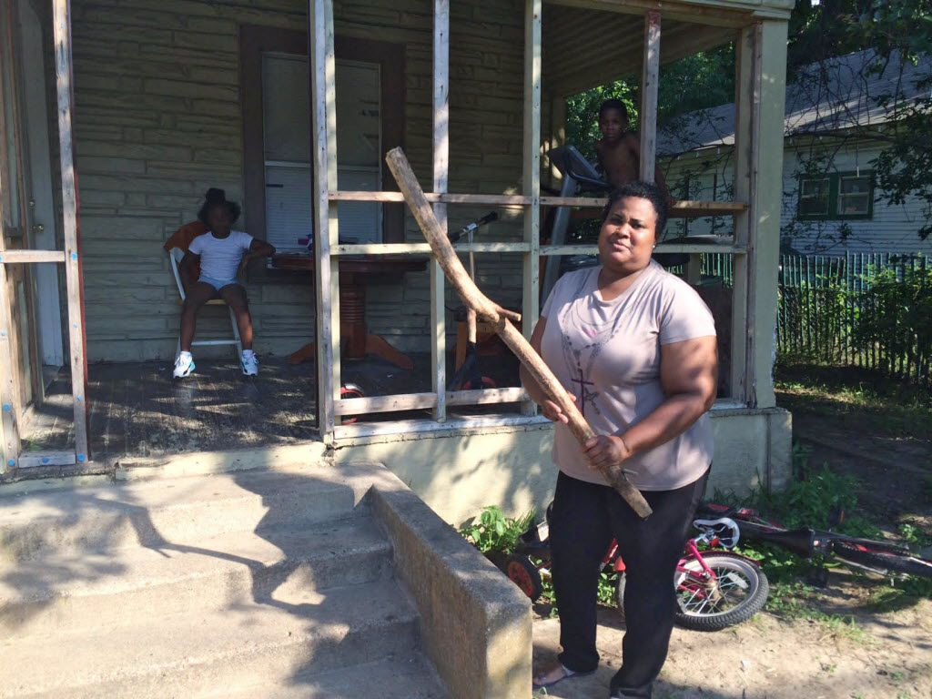Netra Reese, shown in June 2016, keeps this stick by the porch of her Dallas home for protection from the large aggressive dogs who lived across the street and frequently escaped from the backyard to terrorize her and her neighbors – before they allegedly killed Antoinette Brown. (Naomi Martin/Staff Writer)