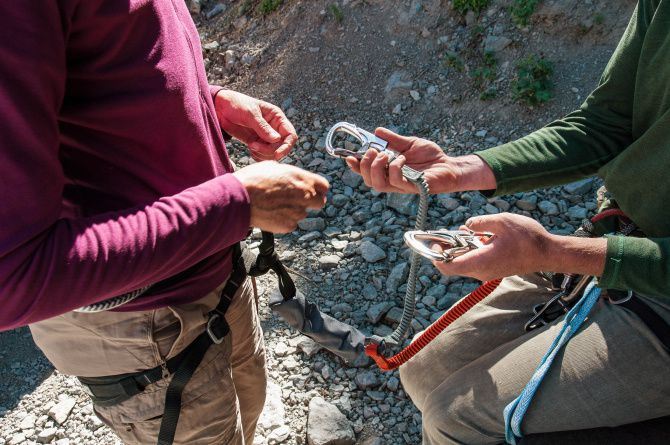 Dianne Leeth receives instruction in the use of dynamic lanyards before starting out on the Via Ferrata in Telluride, Colorado.  The devices keep climbers attached to safety cables and act as shock absorbers should they take a fall.
