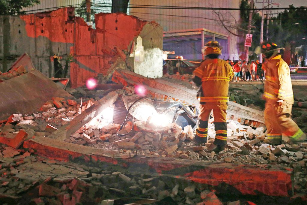 A fence collapsed on a car after the earthquake hit southern Mexico late Thursday. (Agustin Salinas/El Universal)
