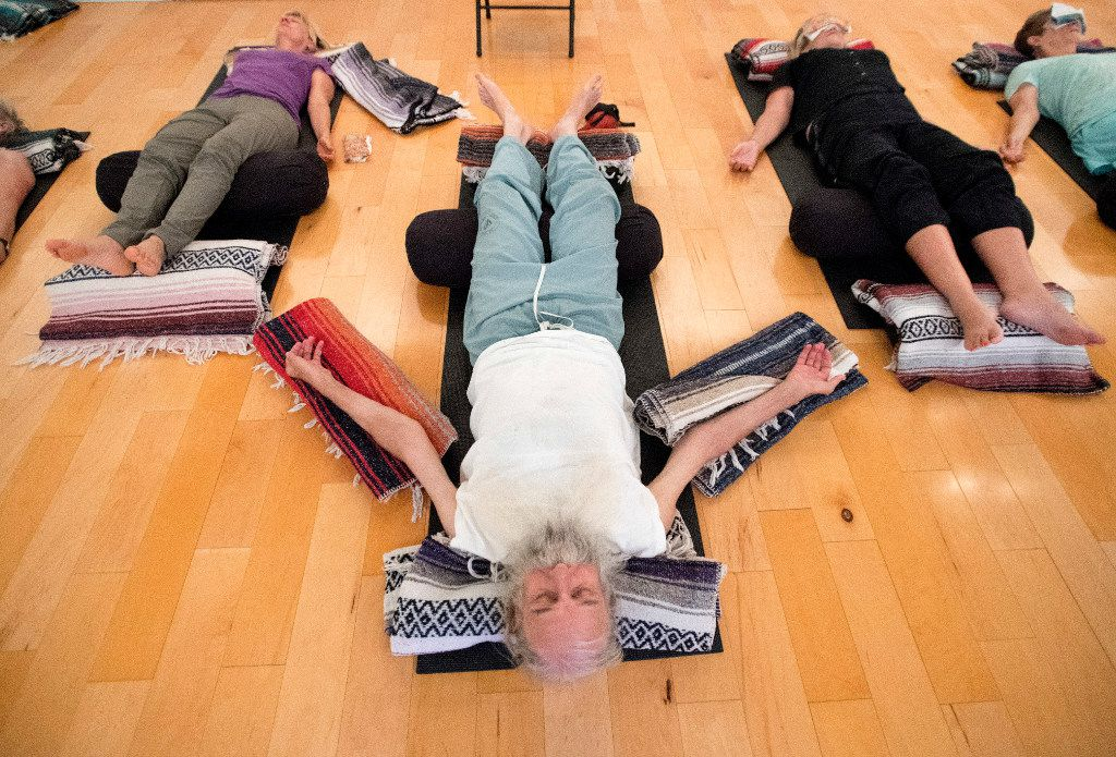 Vietnam veteran Joshua Lloyd, 73, center, practices iRest, a guided meditation experience, during a trauma-sensitive yoga session offered by the non-profit Warrior Spirit Project on Friday, July 21, 2017 at Studio 4 in the Bishop Arts Co-op in Dallas. Warrior Spirit Project seeks to help military veterans and first-responders heal from trauma through yoga, a support dog program, and gardening. (Jeffrey McWhorter/Special Contributor)