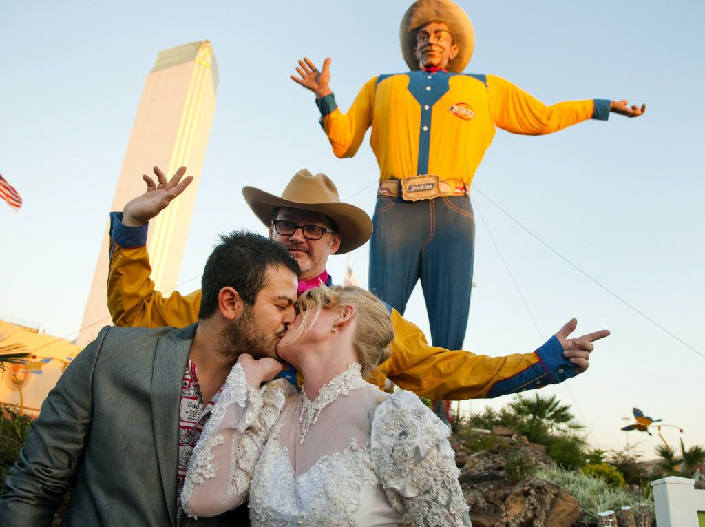 """Jose Luis Martinez Hernandez of Mexico City kisses his wife, Sara Rice of Dallas, after their friend Tom """"Pinky Diablo"""" Sale of Ennis conducted their wedding ceremony in front of Big Tex at the State Fair of Texas in 2010."""