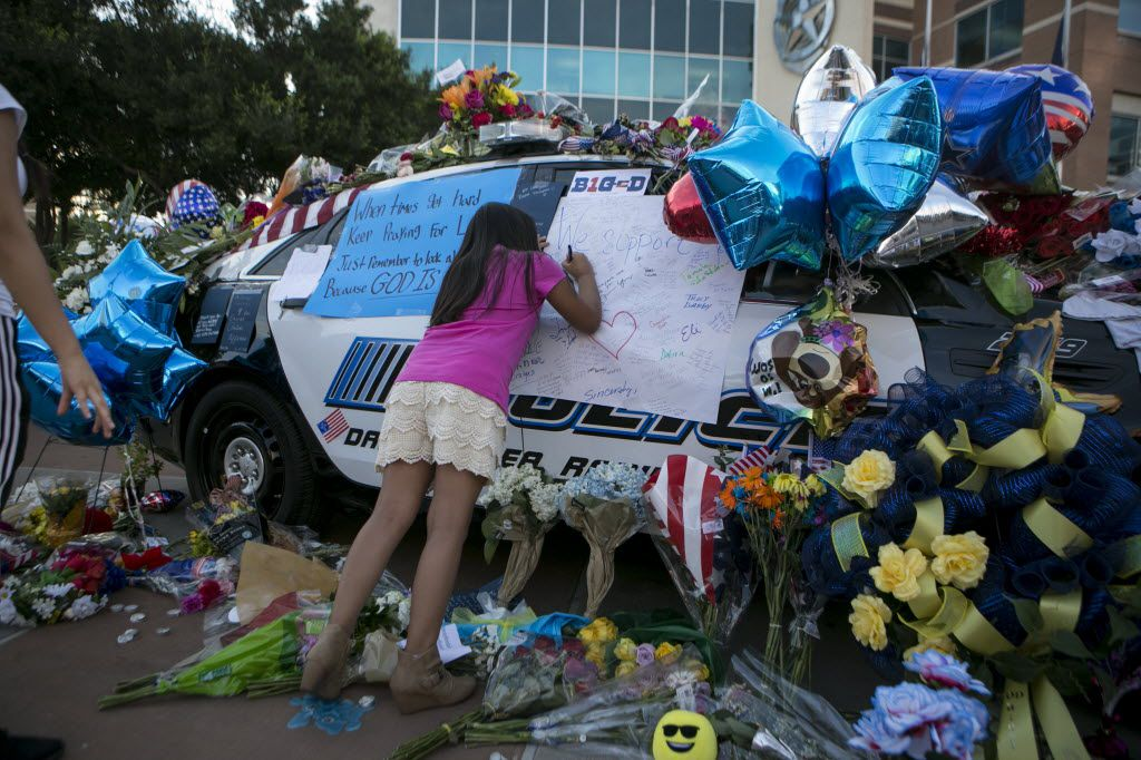 Jasmine Ruiz, 9, left a note Saturday on the makeshift memorial to slain and wounded officers outside Dallas police headquarters. (Ilana Panich-Linsman/The New York Times)
