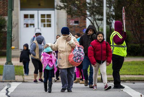Padres y sus hijos cruzan la calle para ingresar a la primaria Auburn, en East Grand Avenue, durante una fría mañana en noviembre. ASHLEY LANDIS/DMN