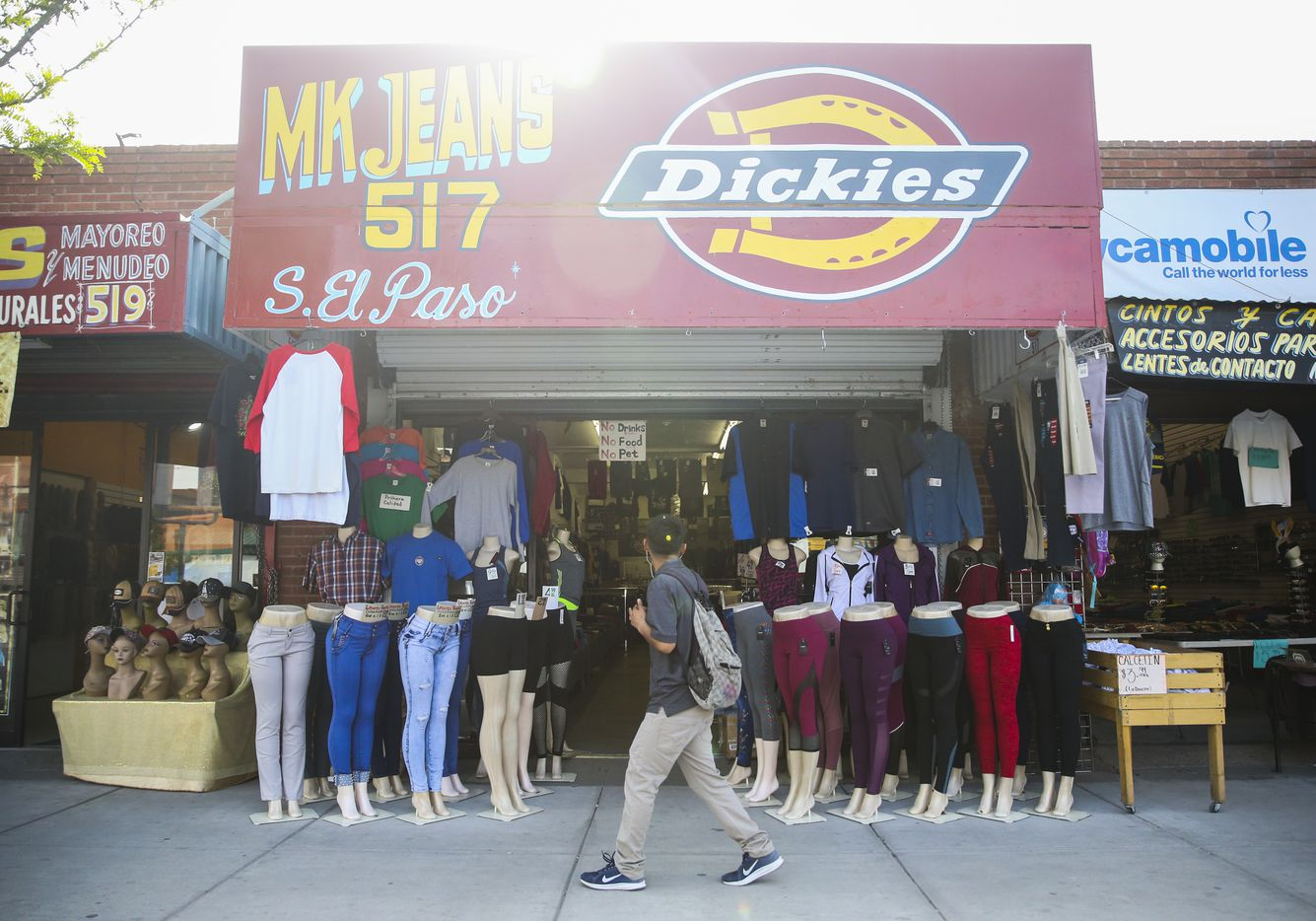 Shoppers pass by clothing stores along El Paso Street in downtown El Paso, Texas, on Monday, April 1, 2019.
