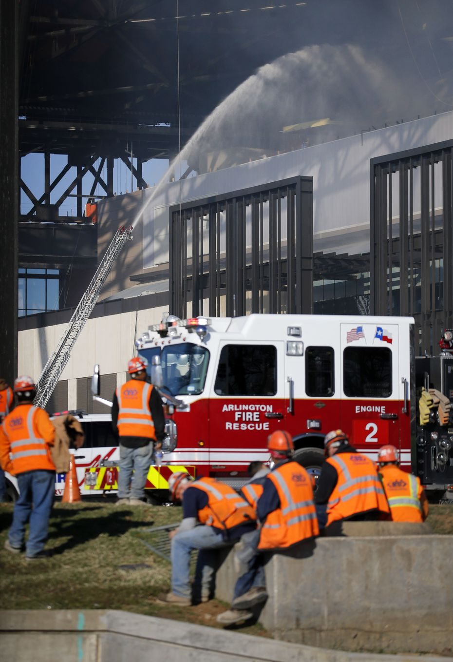 Arlington firefighters try to get a handle on a fire in the upper concourse of the Globe Field Field s construction workers wait and watch outside in Arlington, Texas, Saturday, December 14, 2019.
