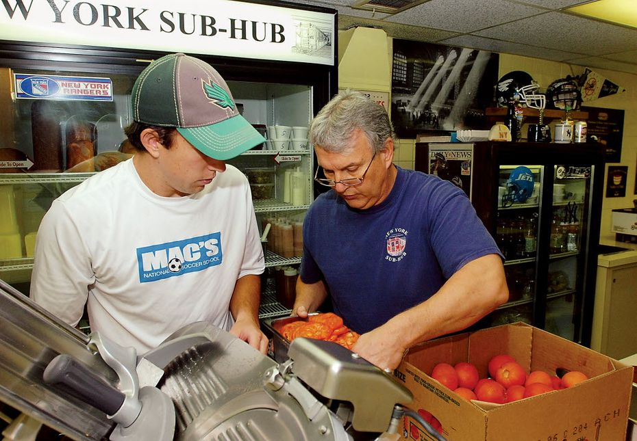 This 2011 file photo shows New York Sub Hub then-owner Ken Christiansen (right) and his son, Hunter, as Hunter was about to take over the family business.