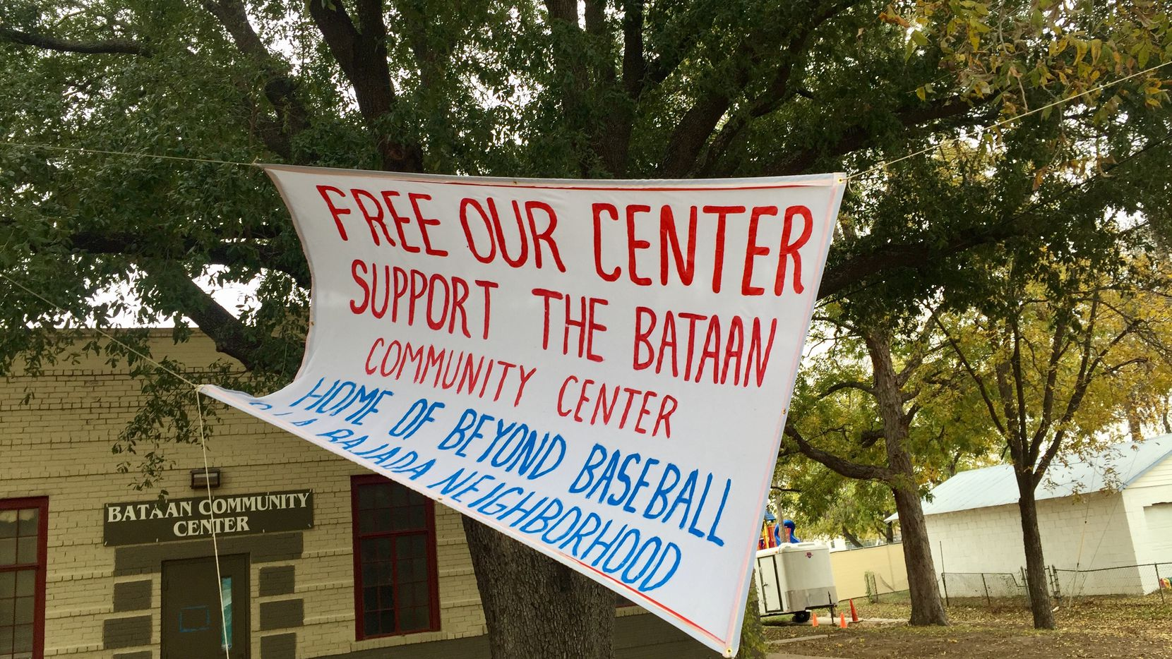 A banner outside the Bataan Community Center highlights the dispute between La Bajada residents and  West Dallas Community Centers Inc., a nonprofit which owns the five-acre venue. Beyond Baseball Youth Association has a 10-year contract to run programs at the center. (Dianne Solis/Staff)