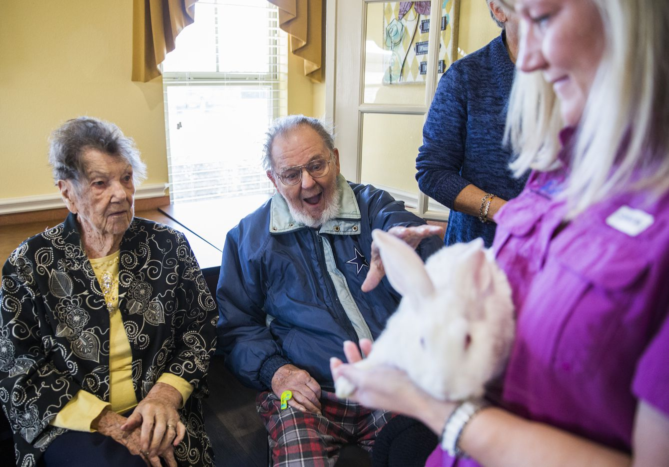 Jerry Holdridge, center, reacts to touching Snow the rabbit as Stacy Danby, right, of ARoo4U takes her around the room at Mustang Creek Estates of Frisco on Friday, January 25, 2019. ARoo4U brought several therapy animals, including a kangaroo, to visit the residents. At left is Geraldine Webb. (Ashley Landis/The Dallas Morning News)